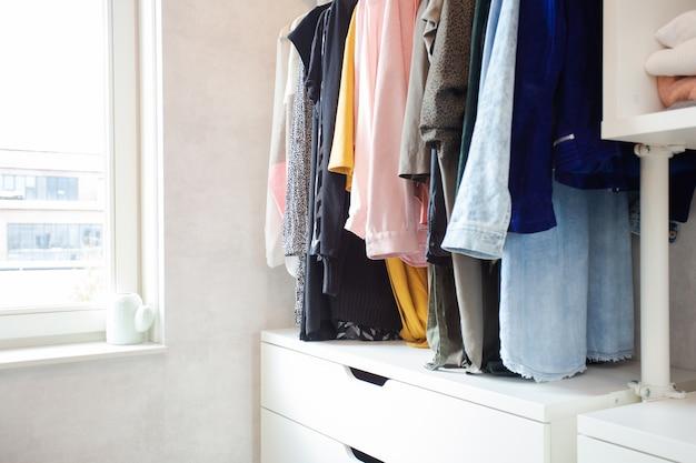 Coleção colorida de roupas femininas penduradas em um armário casual moderno em uma sala iluminada