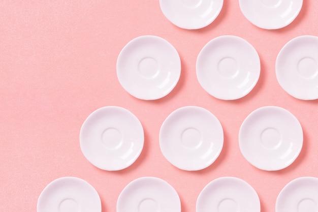 Coleção das placas pequenas brancas em uma superfície cor-de-rosa. copie o espaço. vista do topo