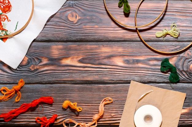 Coleção de acessórios de bordado em um fundo de madeira