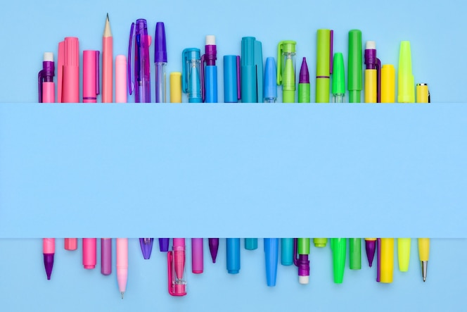 Coleção de artigos de papelaria do arco-íris com canetas e lápis em um fundo azul claro