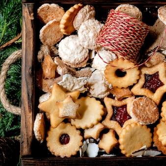 Coleção de biscoitos de biscoitos amanteigados caseiros de natal em ramos de thuja. vista do topo