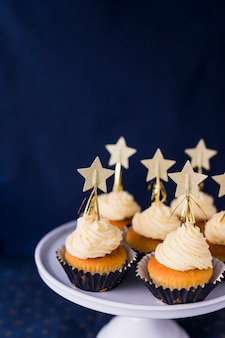 Coleção de bolos saborosos com creme de manteiga e estrelas em stand