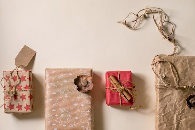 Coleção de caixas de presente de natal em papel artesanal ecológico em fila, decorada com paus de canela sobre fundo de papel bege. conceito de presente de natal eco. postura plana, copie o espaço