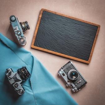 Coleção de câmeras vintage sobre uma lousa em branco com espaço para texto.