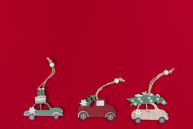 Coleção de carros de brinquedo pendurados em uma árvore de natal em um fundo vermelho