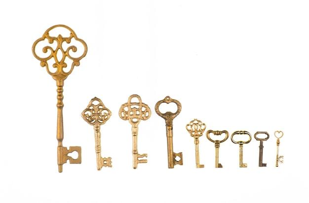 Coleção de chaves douradas antigas isoladas no fundo branco