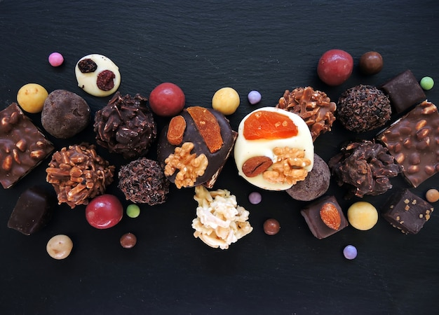 Coleção de chocolates finos em chocolate branco, escuro e ao leite em fundo preto