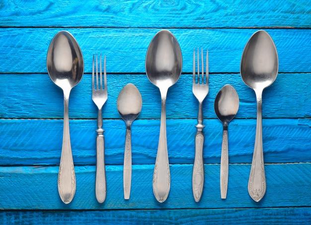 Coleção de colheres e garfos, sobre um fundo azul de madeira. vista do topo.