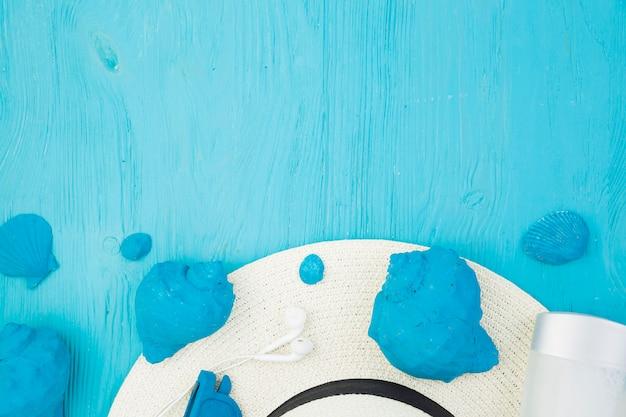 Coleção de conchas azuis perto de chapéu e fones de ouvido