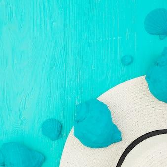 Coleção de conchas azuis perto de chapéu