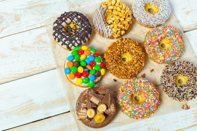Coleção de deliciosos donuts na placa de madeira branca