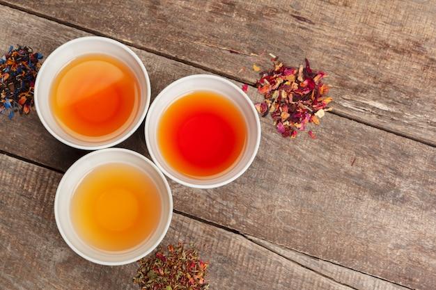 Coleção de diferentes chás em xícaras com folhas de chá