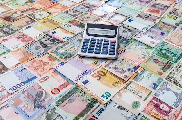 Coleção de dinheiro mundial com calculadora Foto Premium