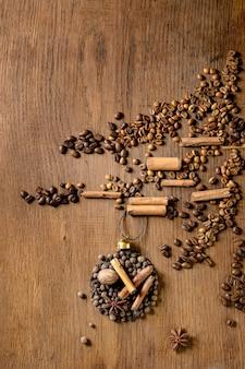 Coleção de especiarias aromáticas como forma de bolas de natal na árvore de natal de diferentes grãos de café sobre fundo escuro de madeira. saudações de natal amantes do café. copie o espaço