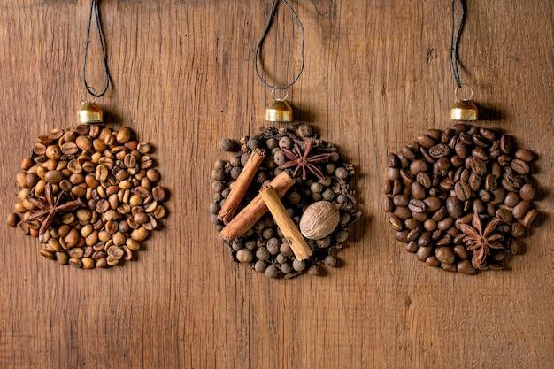 Coleção de especiarias aromáticas e diferentes grãos de café à medida que as bolas de natal se formam em linha. pimenta da jamaica, paus de canela, cravo, noz-moscada torrada em grãos de arábica sobre fundo escuro de madeira. cartão de felicitações de natal