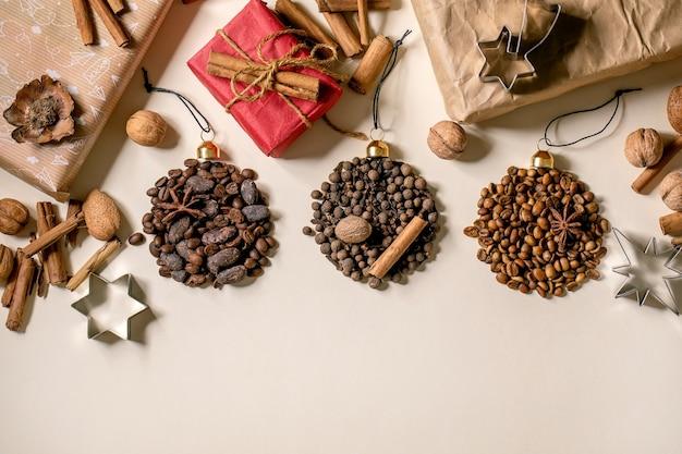 Coleção de especiarias aromáticas e diferentes grãos de café em forma de bolas de natal e caixas de presente de natal ecológicas sobre fundo de papel bege. saudações natal amantes do café