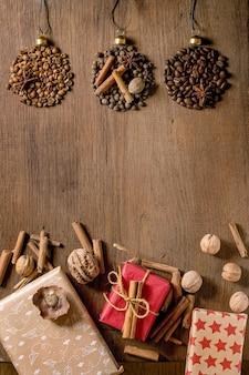Coleção de especiarias aromáticas e diferentes grãos de café em forma de bolas de natal e caixas de presente de natal ecológicas sobre fundo escuro de madeira. saudações natal amantes do café
