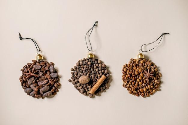 Coleção de especiarias aromáticas e diferentes grãos de café em forma de bolas de natal. pimenta da jamaica, paus de canela, cravo, noz-moscada torrada em grãos de arábica sobre fundo de papel bege. saudações natal amantes do café