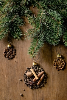 Coleção de especiarias aromáticas e diferentes grãos de café em forma de bolas de natal. pimenta da jamaica, paus de canela, cravo, noz-moscada torrada em grãos de arábica sobre fundo escuro de madeira. saudações natal amantes do café