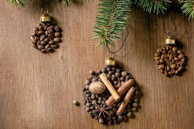 Coleção de especiarias aromáticas e grãos de café diferentes como forma de bolas de natal em galho de árvore do abeto sobre fundo escuro de madeira. conceito de amantes do café saudações de natal