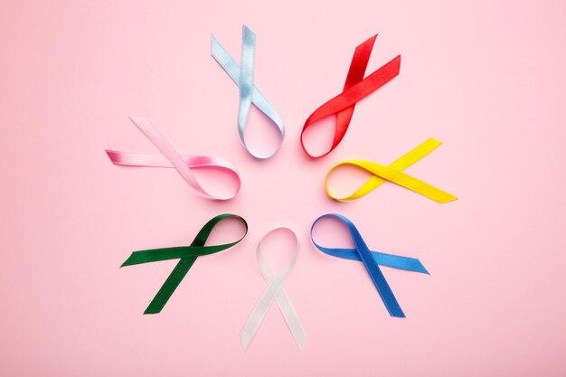 Coleção de fitas de conscientização em superfície rosa pastel