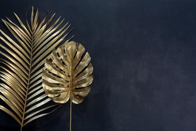 Coleção de folhas tropicais na cor dourada no fundo do espaço preto. desenho abstrato de decoração de folhas