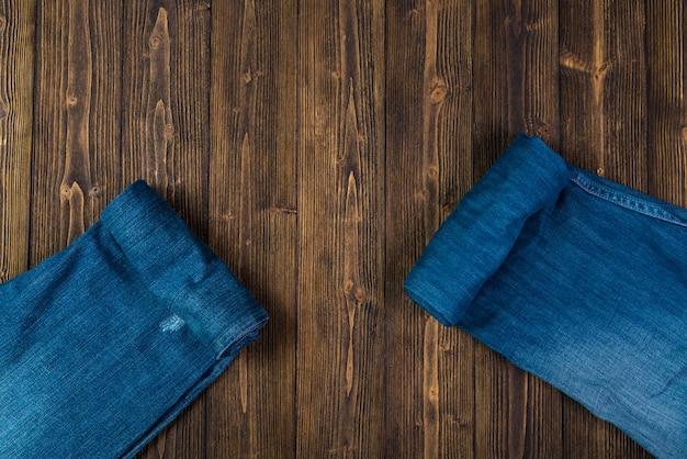Coleção de jeans desfiados ou jeans azul sobre madeira escura áspera