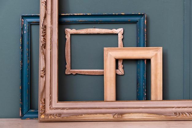 Coleção de molduras vintage de madeira retangulares vazias variadas em pé contra uma parede cor de azul-petróleo