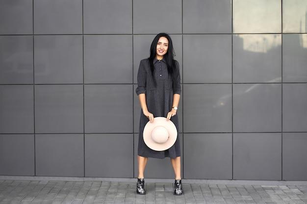 Coleção de outono na moda. feliz menina morena linda elegante vestido cinza com chapéu elegante nas mãos. modelo com roupa da moda posando na parede cinza. retrato ao ar livre.