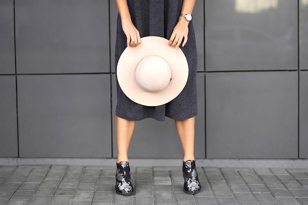 Coleção de outono na moda. feliz menina morena linda elegante vestido cinza segurando chapéu elegante nas mãos. modelo com roupa da moda posando no fundo da parede cinza. retrato ao ar livre.