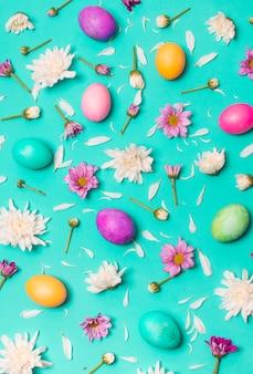 Coleção de ovos brilhantes entre botões de flores