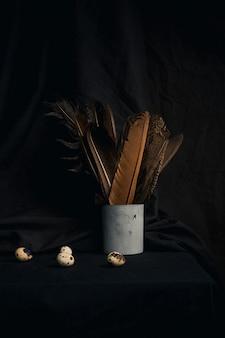 Coleção de ovos de codorna perto de penas em lata