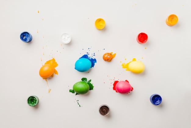 Coleção de ovos de páscoa perto de cores de água