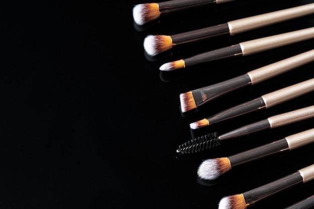 Coleção de pincéis de maquiagem em fundo preto, close-up