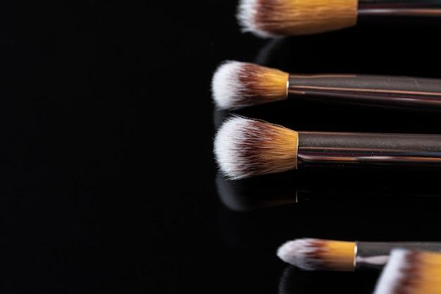 Coleção de pincéis de maquiagem na superfície preta
