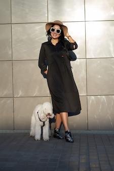 Coleção de primavera. menina bonita morena feliz usando vestido preto elegante e elegantes óculos de sol posando com cachorro fofo. modelo com roupa da moda posando no fundo da parede cinza. retrato ao ar livre.