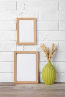 Coleção de quadros em branco na parede e ao lado do vaso