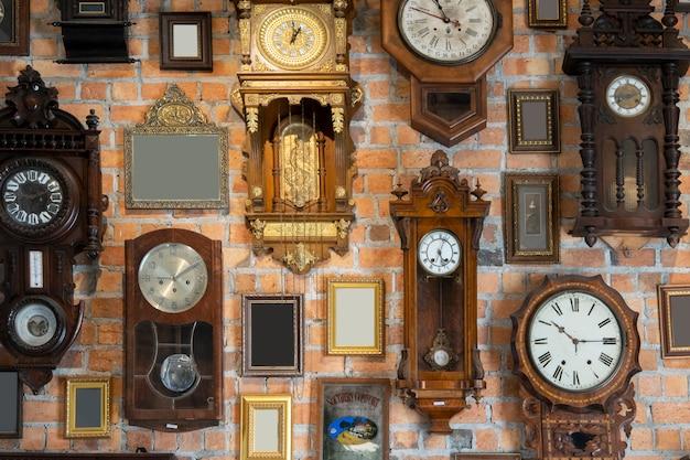 Coleção de relógio vintage e porta-retrato pendurado em uma parede de tijolo