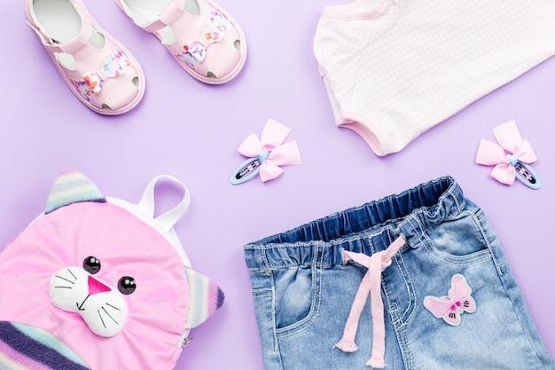 Coleção de roupas plana lay com camiseta, jeans, sandálias, mochila em pastel
