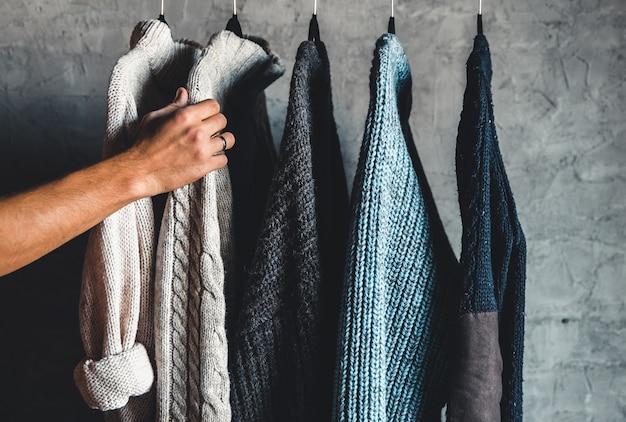 Coleção de suéteres quentes pendurada no suporte contra um fundo cinza, close-up