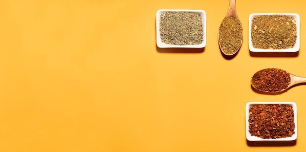 Coleção de três especiarias em colheres de madeira e tigelas brancas em fundo laranja
