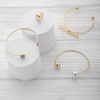 Coleção de três pulseiras e anel em plataformas brancas na madeira com espaço de cópia