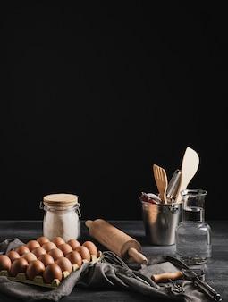 Coleção de utensílios de cozinha ao lado do pacote de ovos