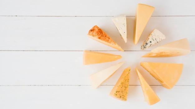 Coleção de vários tipos de queijo na prancha de madeira branca
