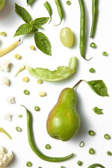 Coleção de vegetais verdes e frutas na mesa branca