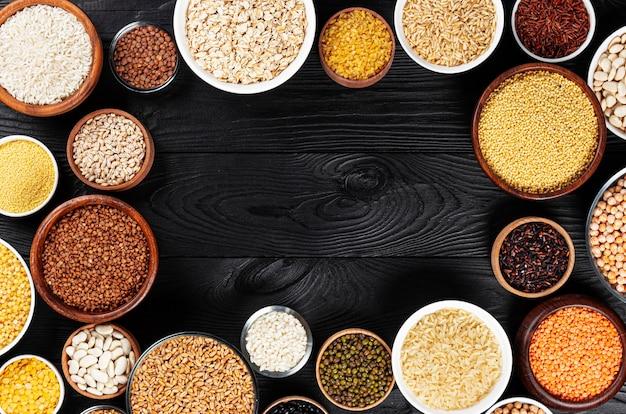 Coleção diferente de cereais, grãos, sementes, sêmolas, legumes e feijões em tigelas, vista superior do mingau cru no fundo preto de madeira com espaço de cópia