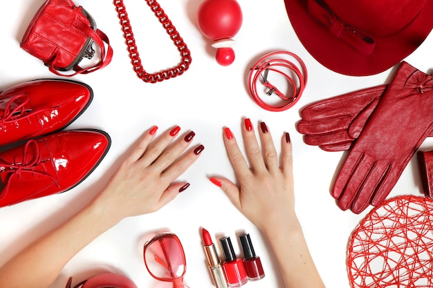 Coleção diversificada de roupas e acessórios em vermelho sobre um fundo branco.