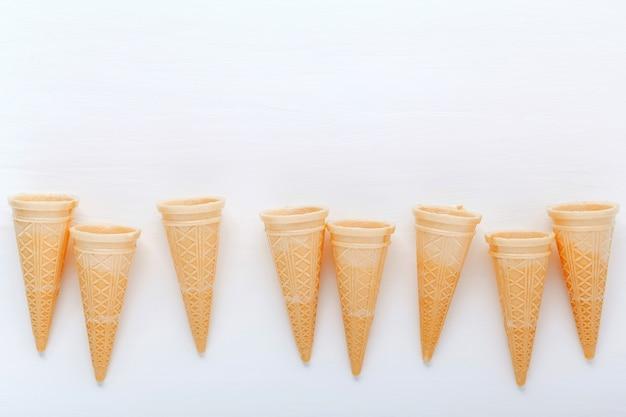 Coleção lisa dos cones de gelado da configuração no fundo de madeira para o projeto do menu dos doces.