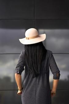 Coleção moderna. menina morena usando vestido cinza elegante e chapéu na moda. modelo com roupa da moda posando no fundo da parede cinza. vista de trás.