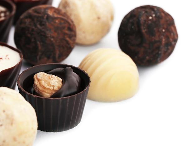Coleção variada de bombons e doces de chocolate, isolada na superfície branca, close-up